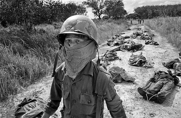 Soldado sudvietnamita, en el fondo soldados estadounidenses y vietnamitas muertos, 1965